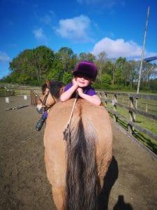Girl lying on horse