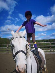 Girl standing on horse